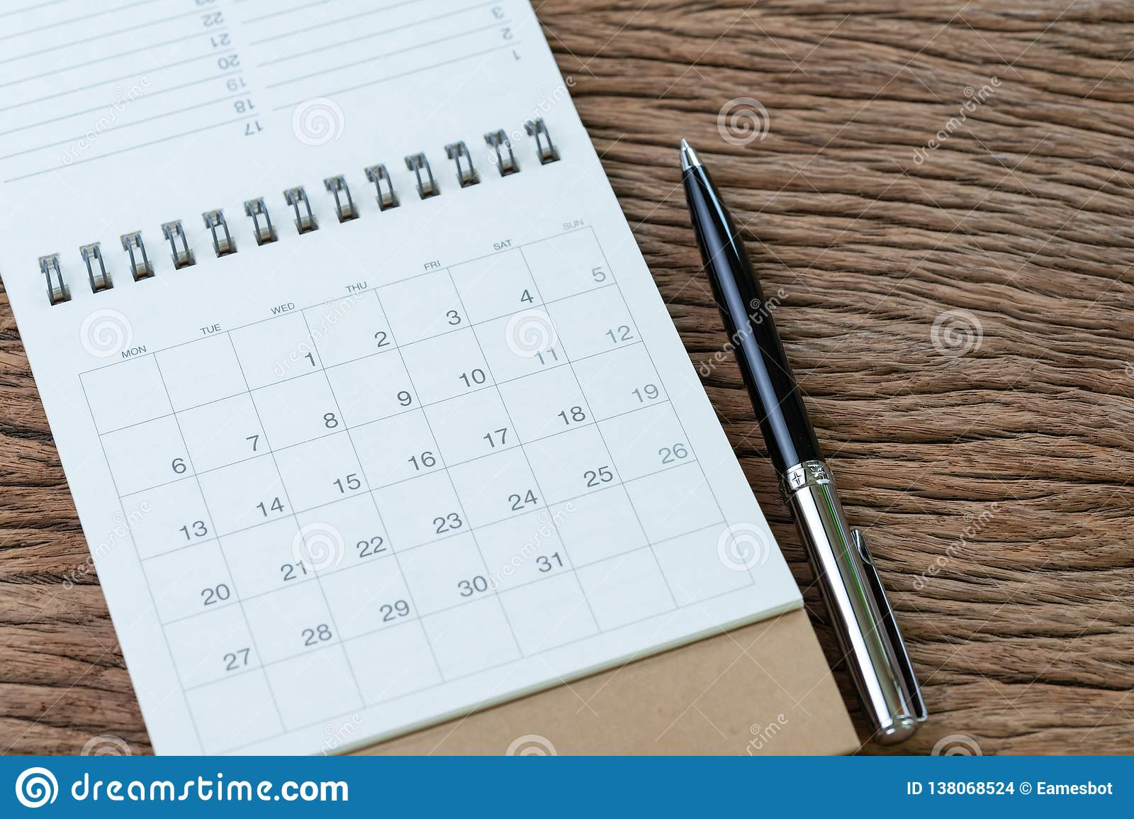 White clean calendar with pen on wooden table background using for business reminder, travel schedule or project planning concept