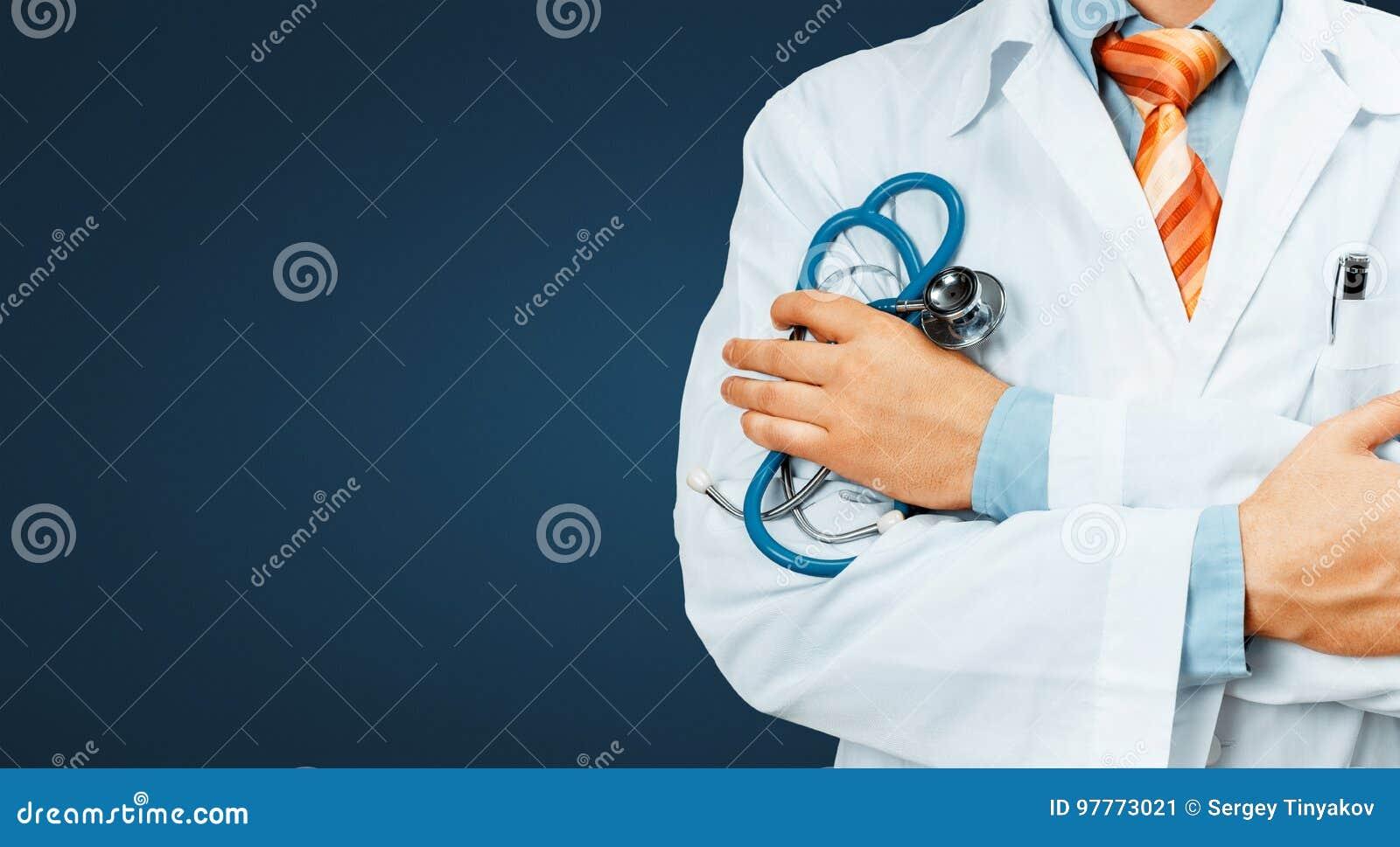 医治In White Coat With听诊器十字架他的在他的胸口拷贝空间的胳膊在蓝色背景 医疗保健医学概念