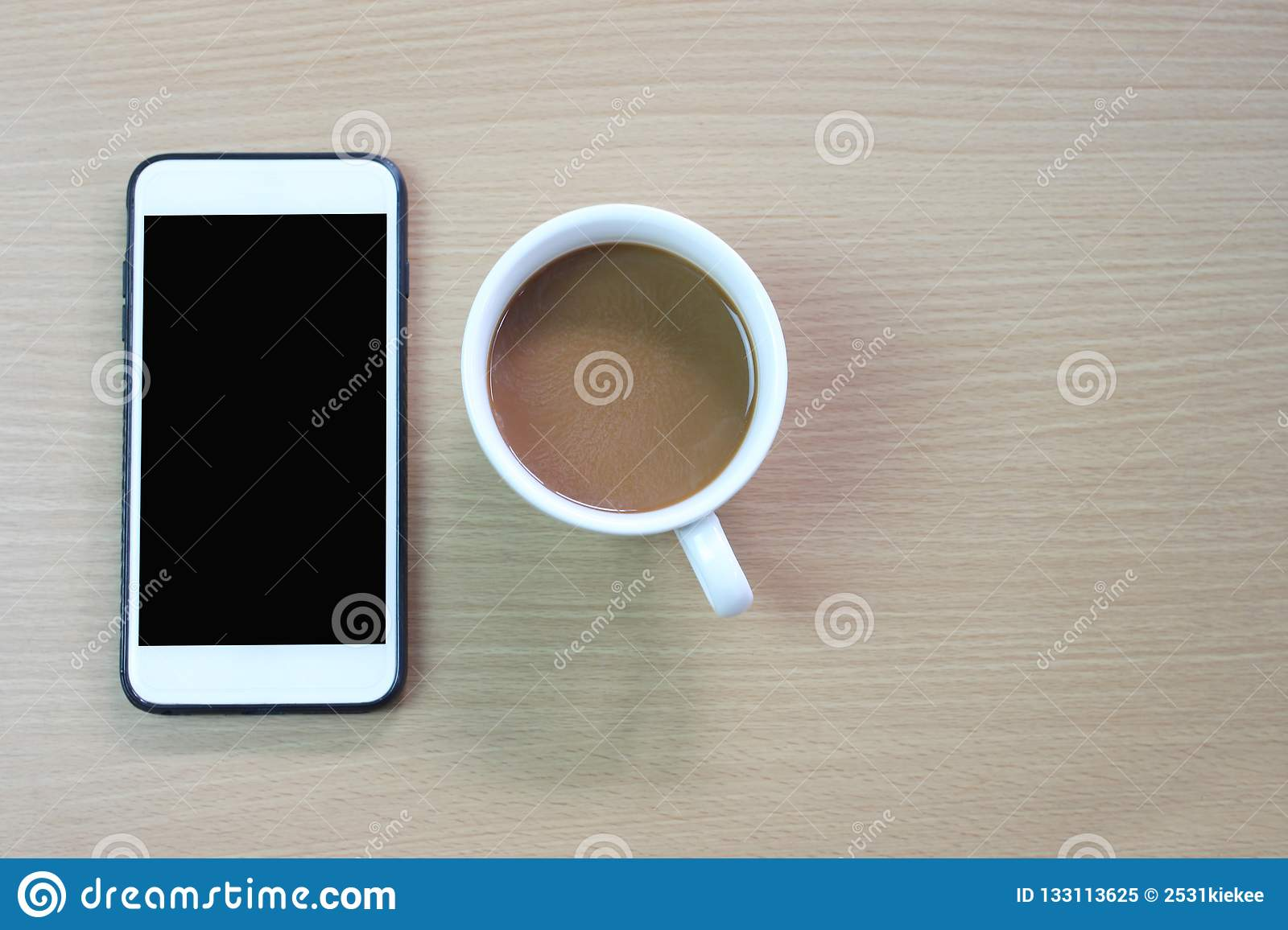 white coffee mug and blank screen of smartphone on a brown wooden floor.