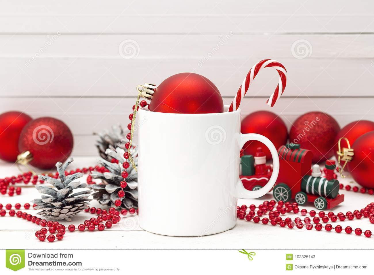 white coffee mug with candy cane and christmas decorations on wh