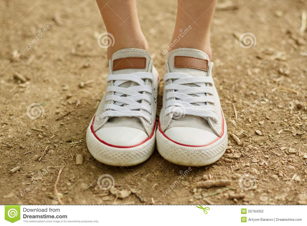 Close-up photo of girl s legs in white converse on ground background 4b528fd7d