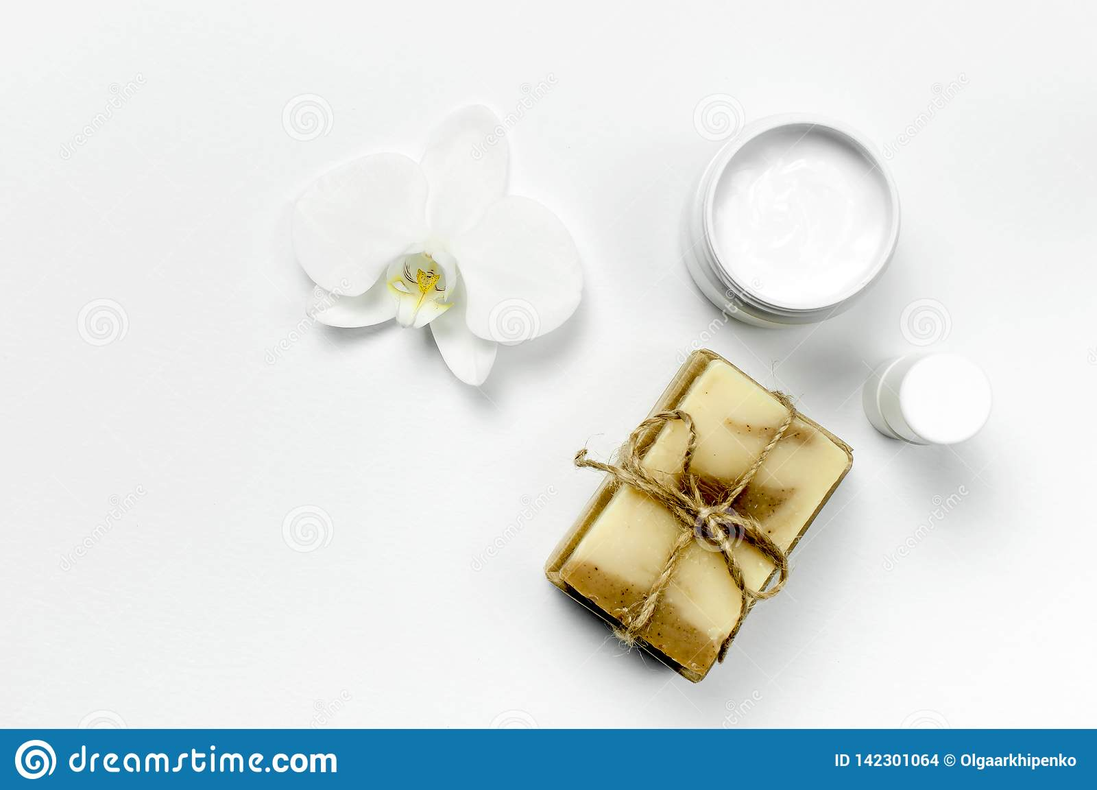 White cosmetic bottle containers, natural soap, orchid flower on white background top view flat lay. Cosmetics SPA branding mock-