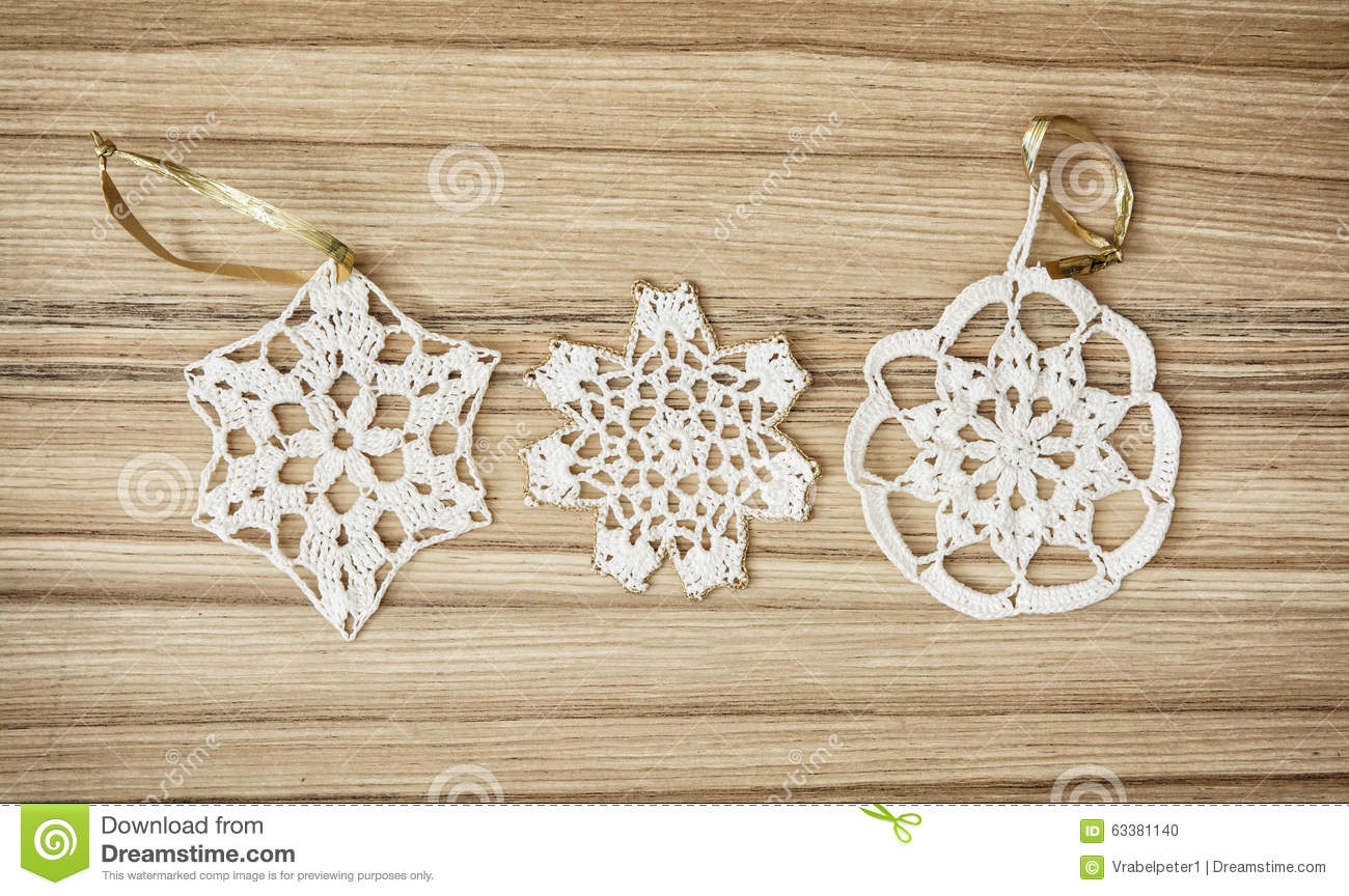white crochet christmas decorations on the wooden background stock