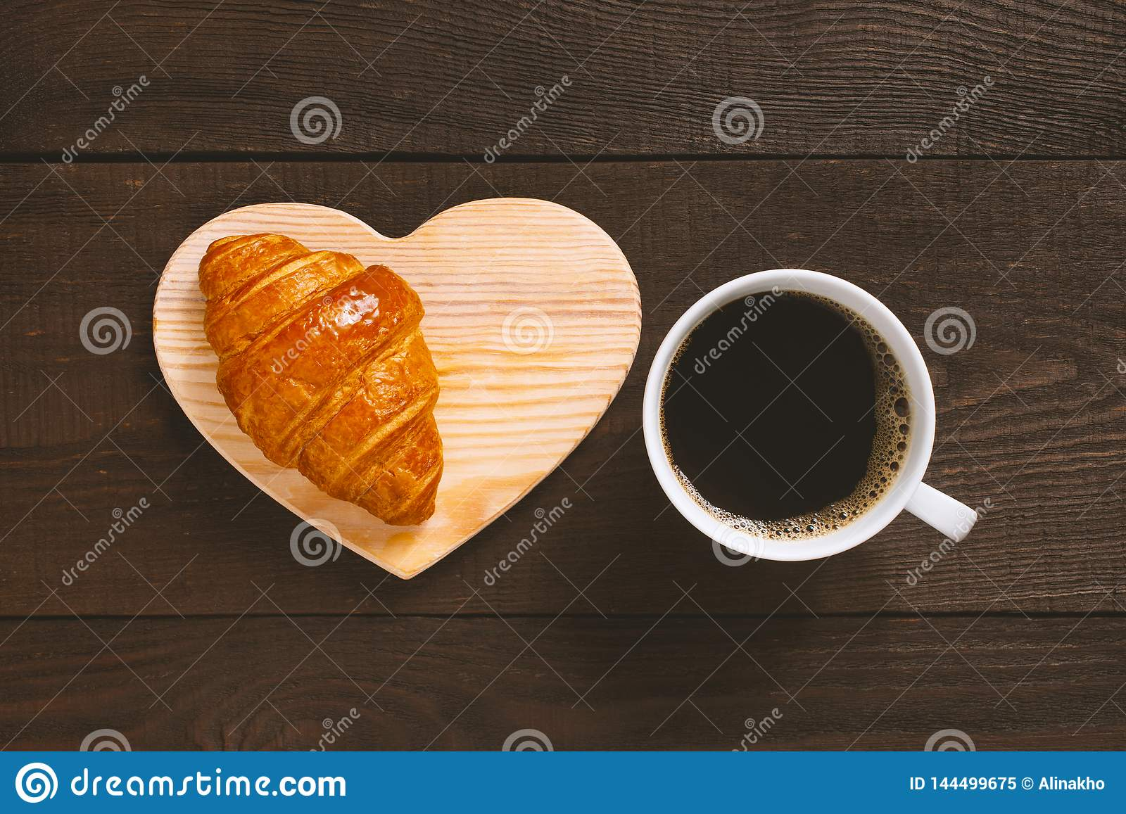 White cup of black coffee with fresh croissant
