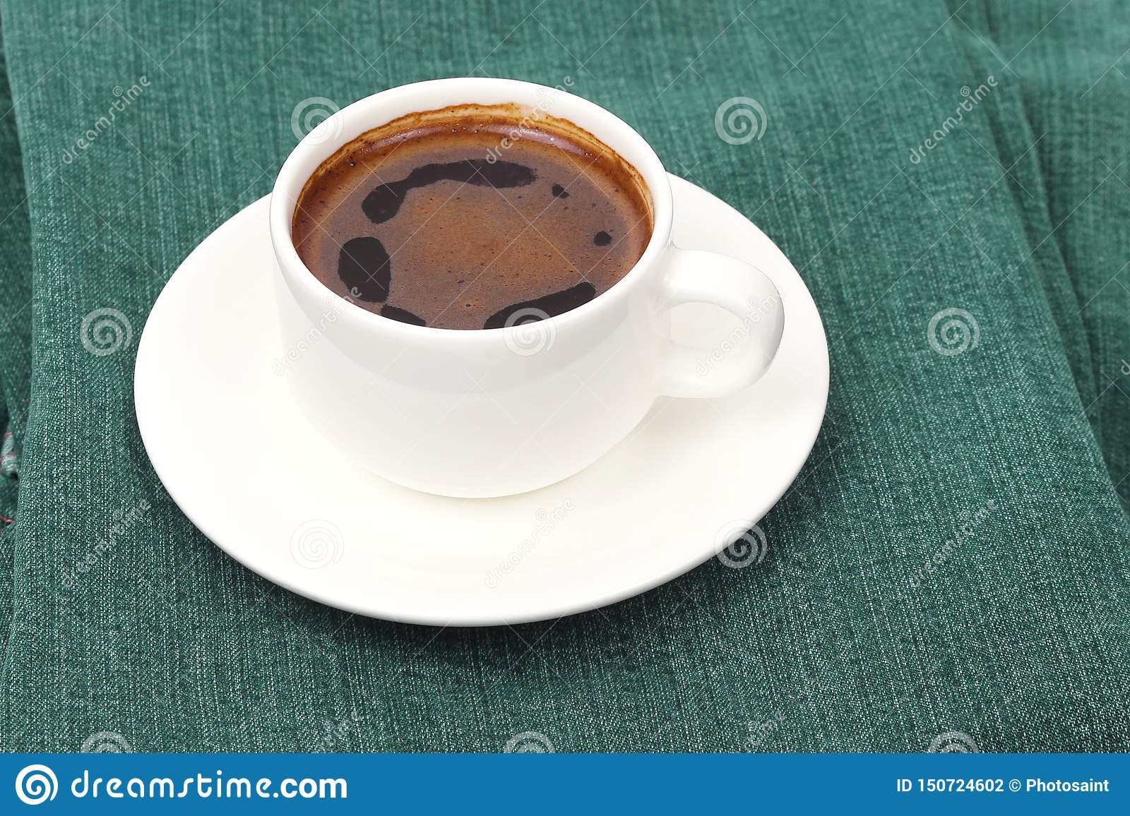 White Cup of black coffee rests on denim pants