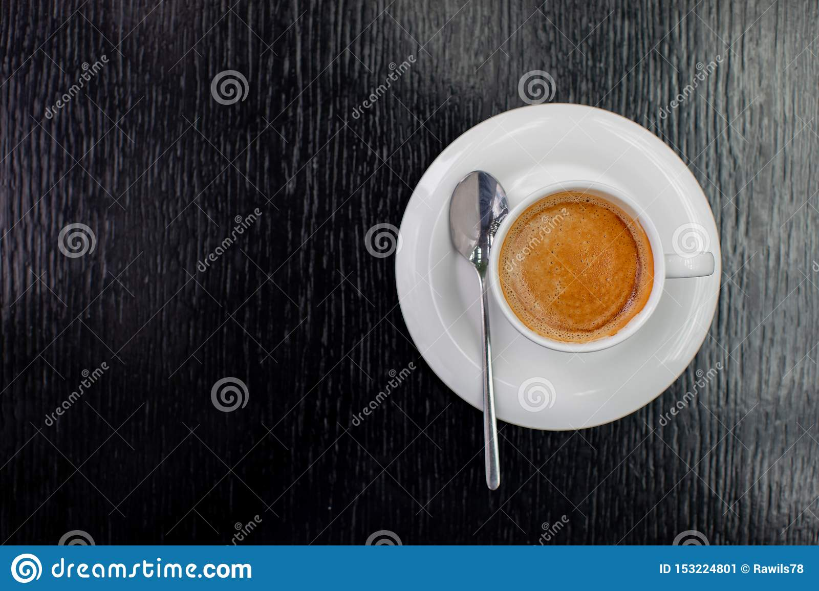 White Cup of cappuccino or expresso coffee with foam on the table in a cafe with a spoon