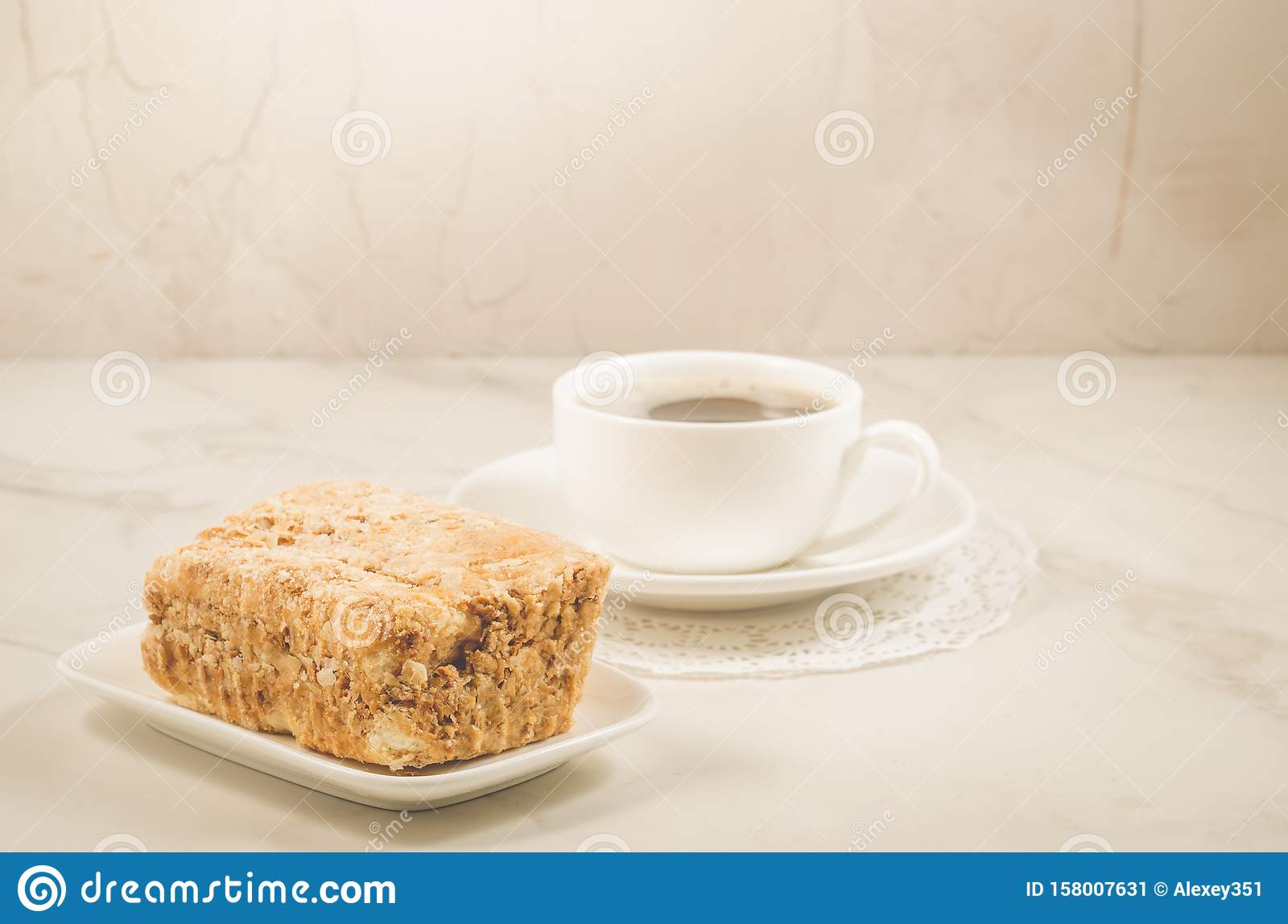 white cup of coffee and dessert/white coffee cup and biscuit on a white marble background. Selective focus