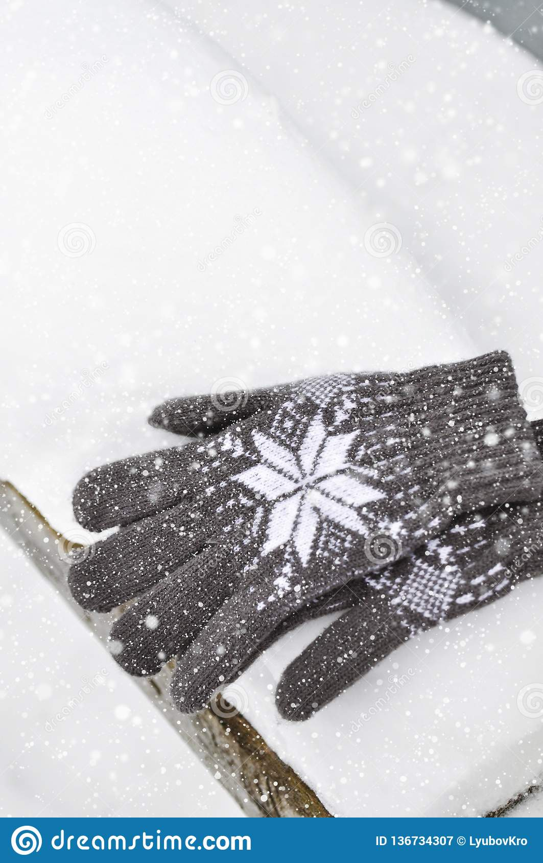 A white Cup of coffee and knitted gray gloves with a pattern on a wooden bench in the snow during a snowfall. Cozy