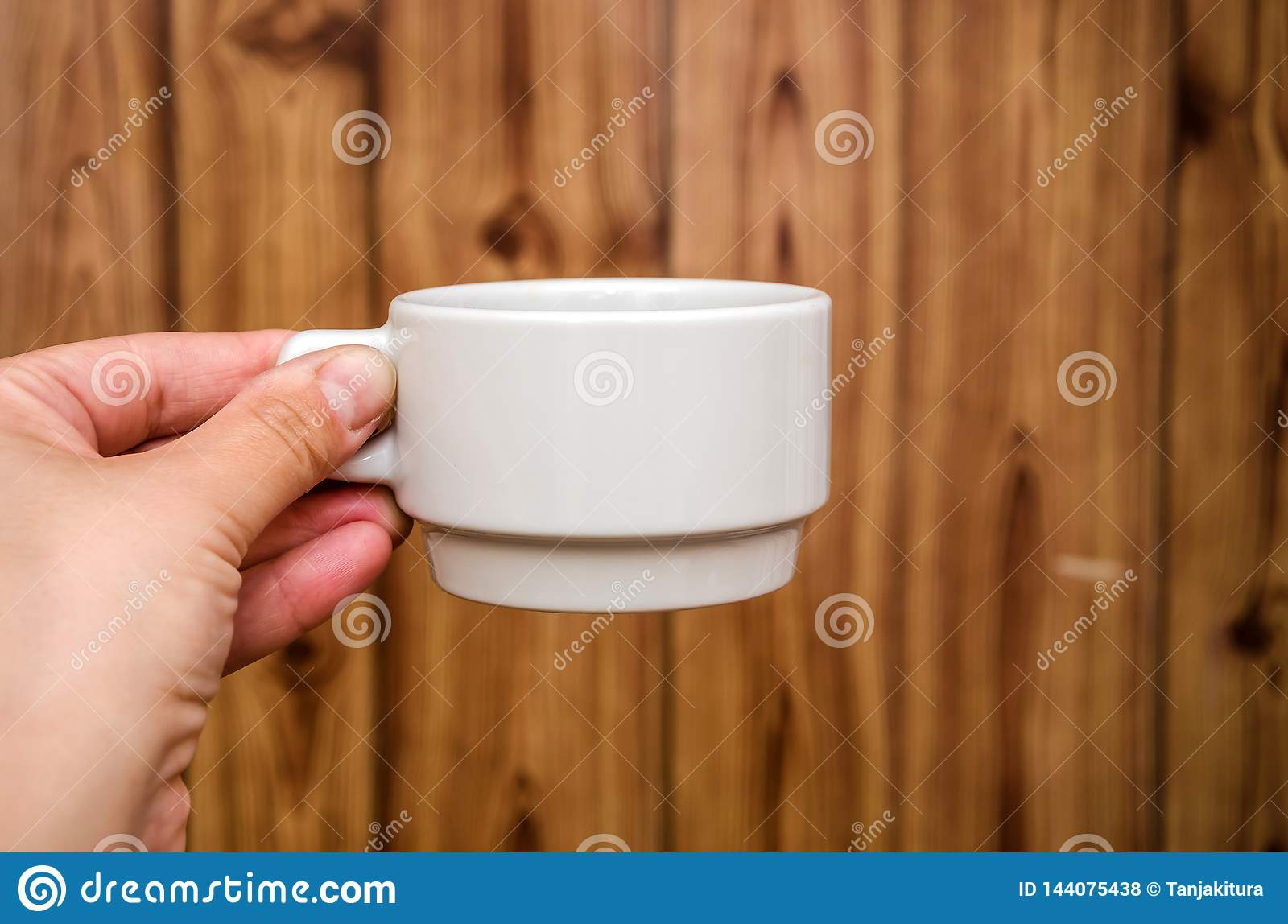 White cup in hand on wooden background