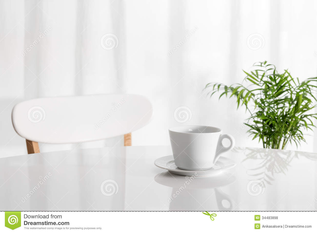white cup on the kitchen table with green plant in the background. Interior Design Ideas. Home Design Ideas