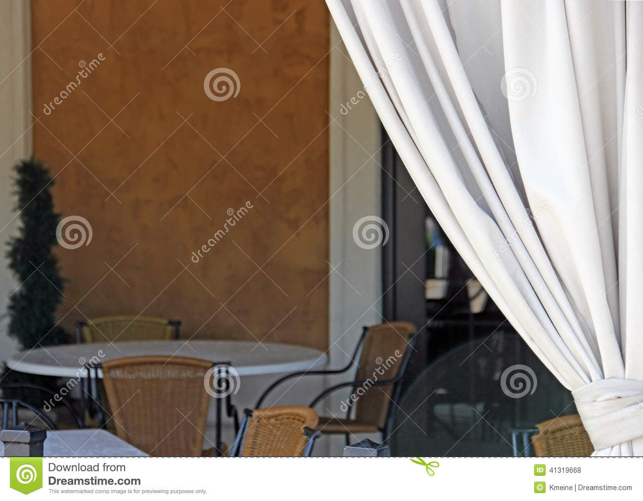 White curtain pulled to invite one to empty outdoor dinner table