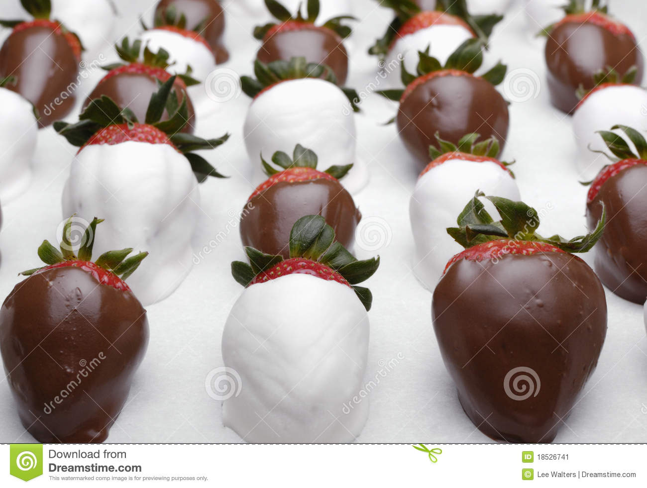 Hand dipped white and dark chocolate covered strawberries on white ...