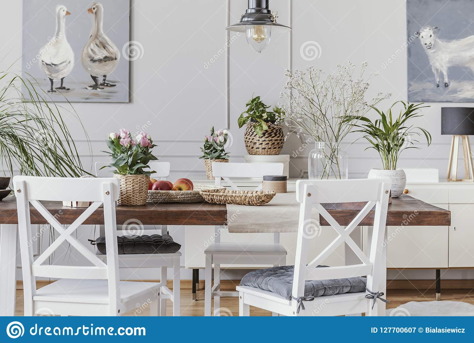 White dining room interior with posters and chairs at wooden table with flowers. Real photo