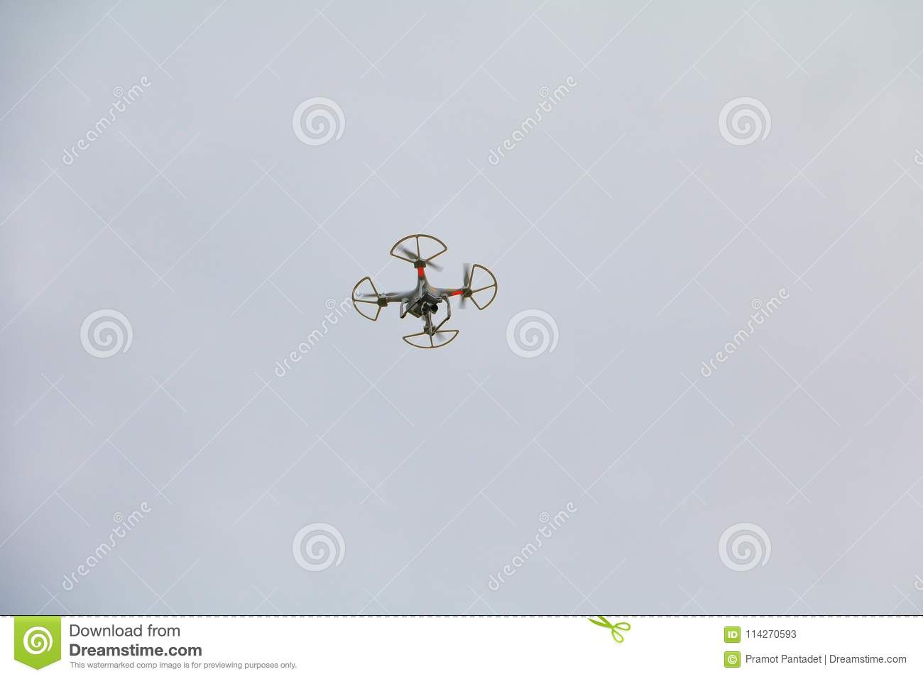White drone motion hovering with photo camera flying in sky