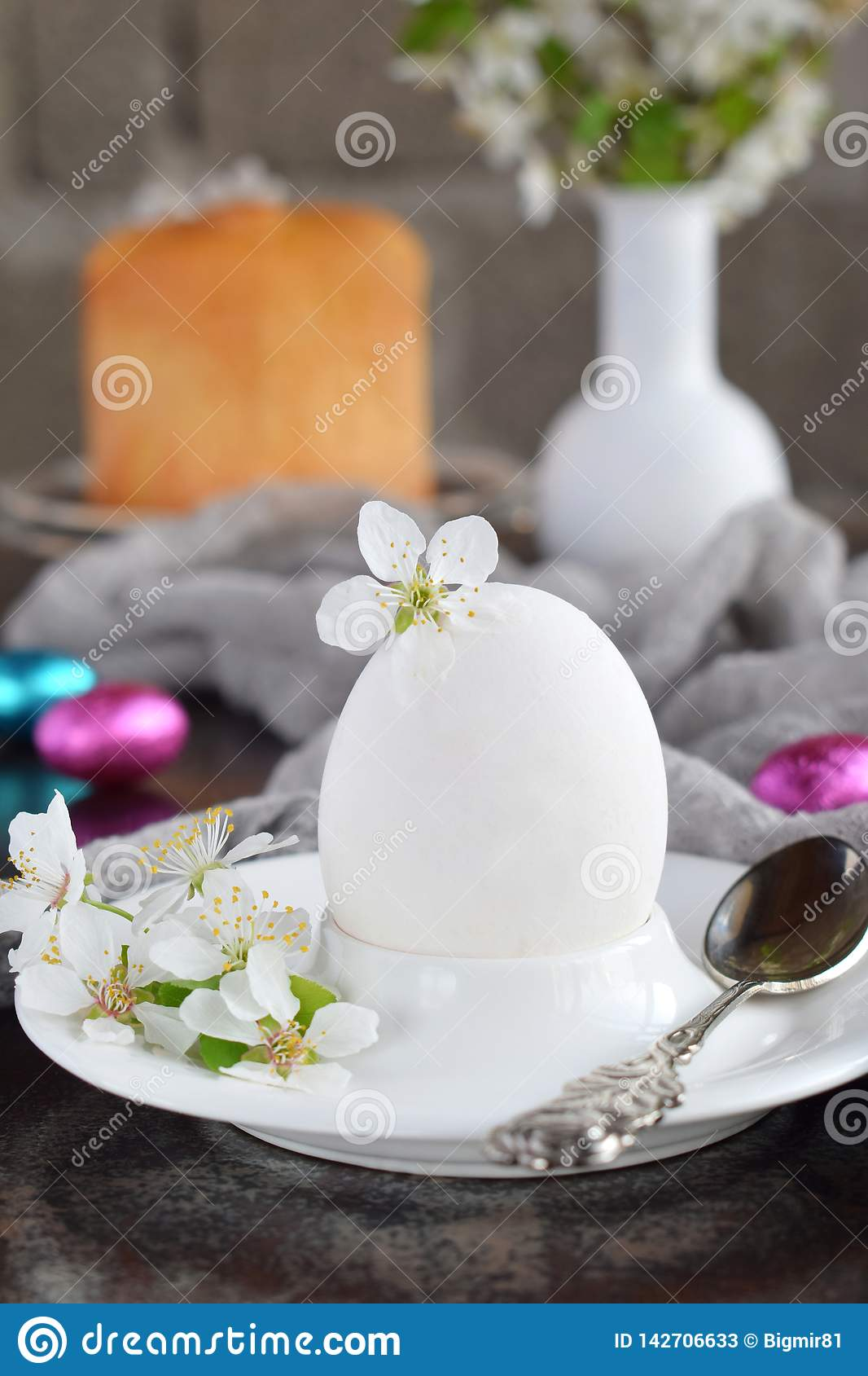 White egg and flowers on clay plate. Happy Easter card. Holidays breakfast concept. Festive table place setting decoration with