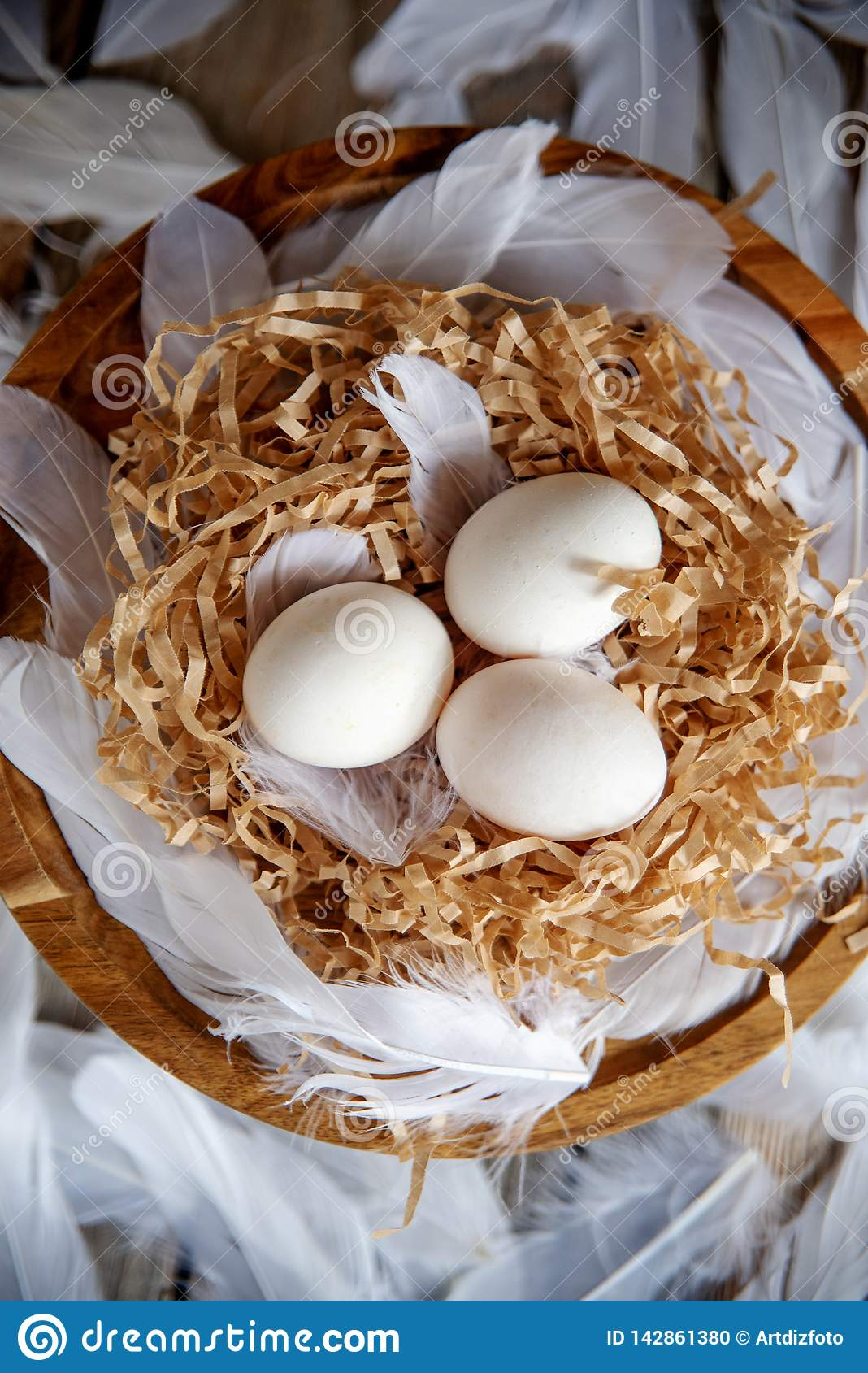 White eggs in a decorative nest on a wooden plate. Easter concept Easter mood