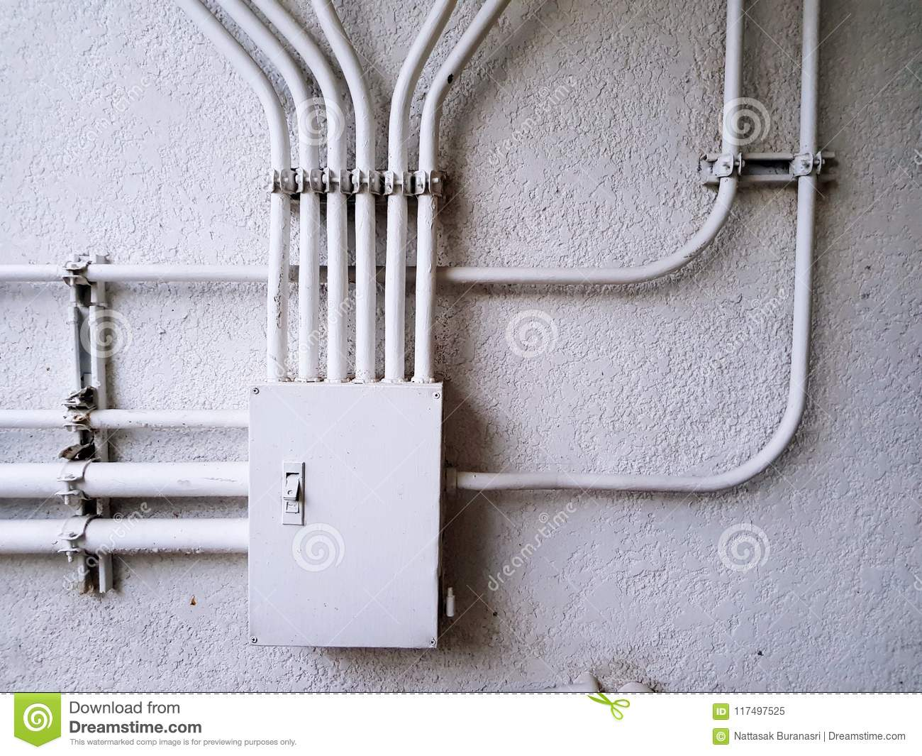 White electrical control junction box for distribution power line on the white concrete wall with copy space