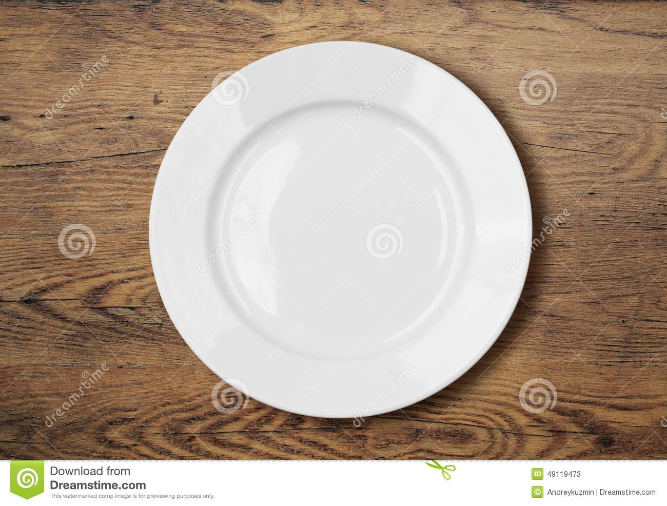 White empty dinner plate on wooden table surface