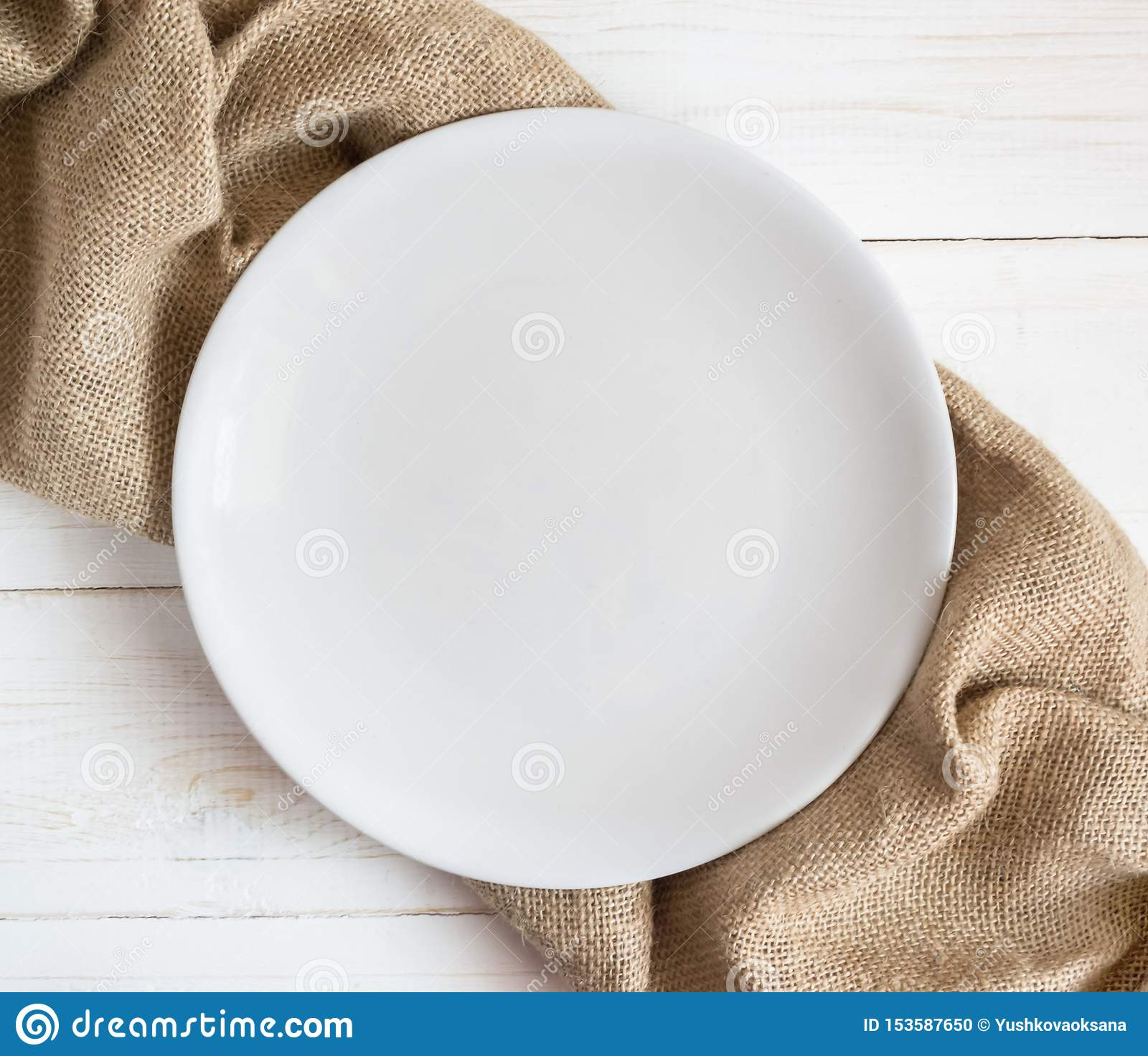 White empty plate on wooden table with brown napkin
