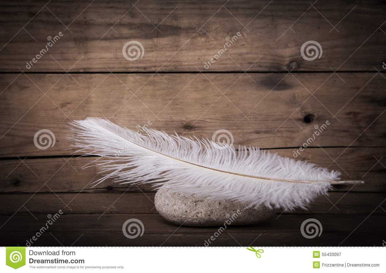White feather and a stone on wooden dark background for mourning