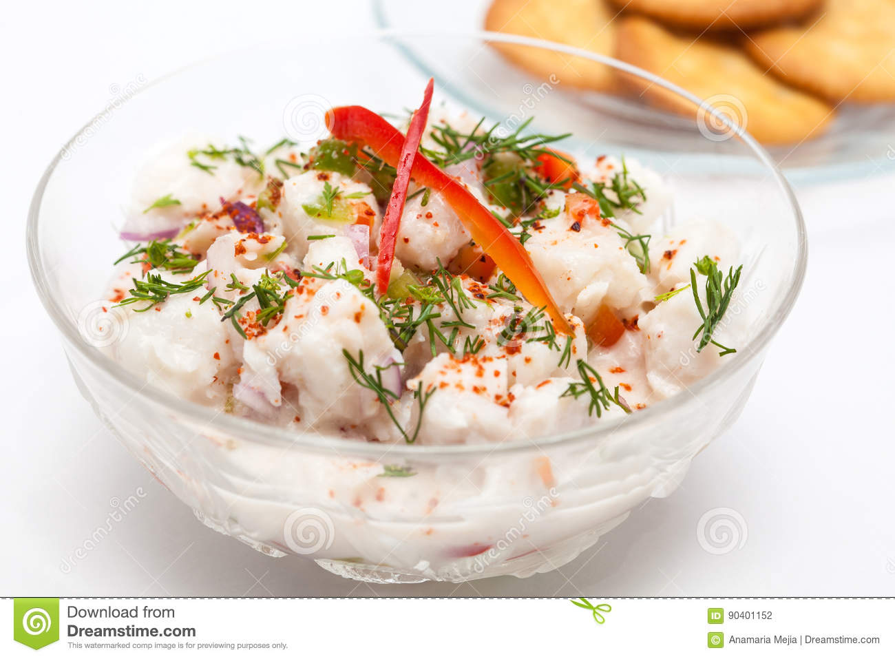 White fish Peruvian ceviche served in a transparent bowl with crackers