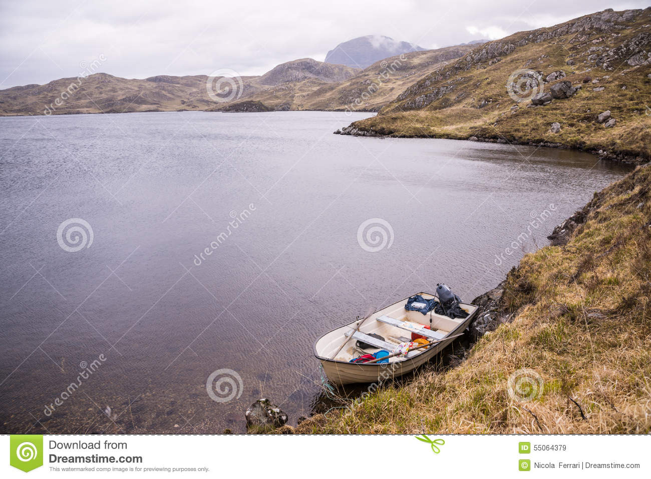 white fishing boat near the shore of a wild loch stock