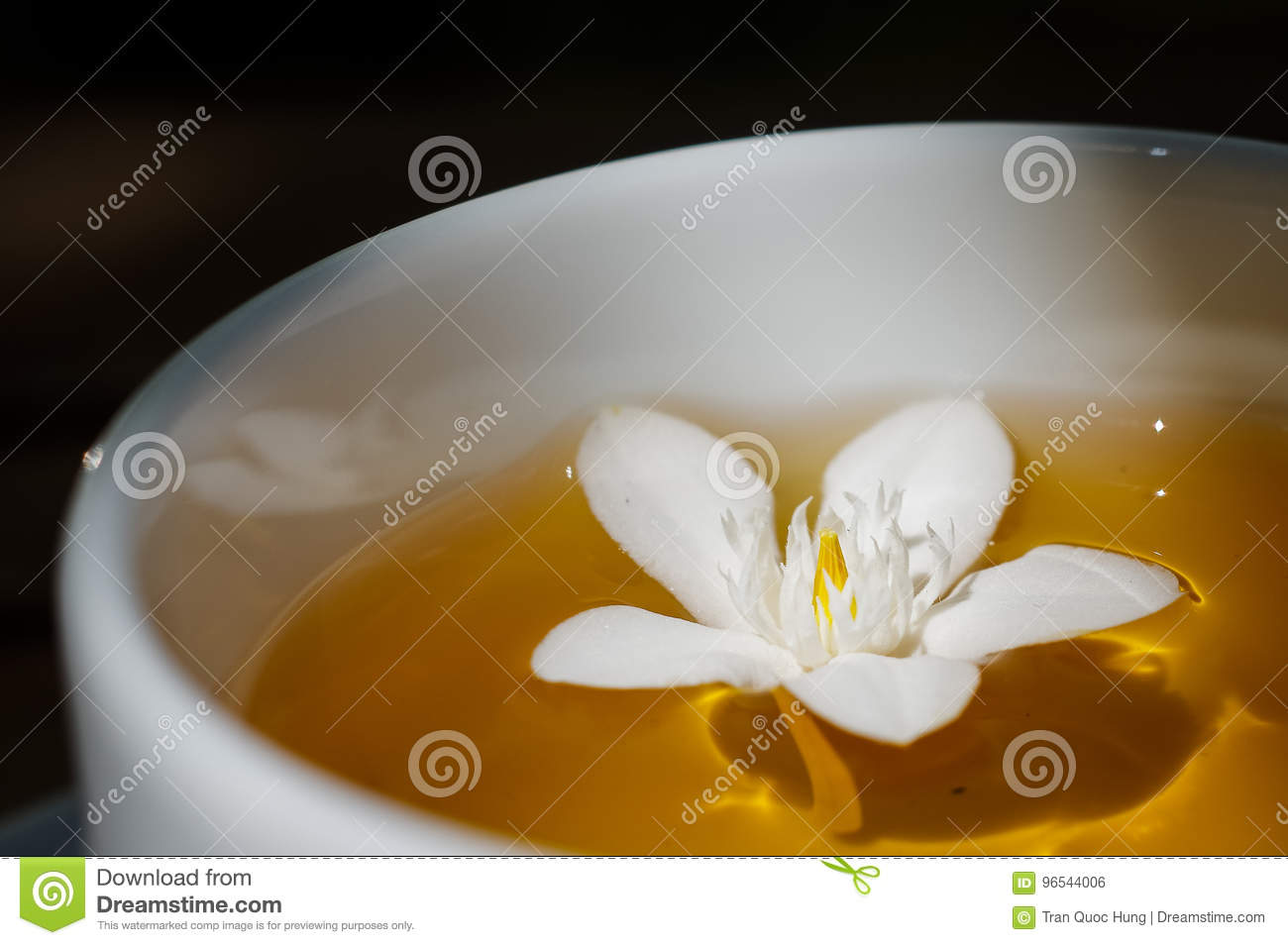 White flower is floating in a cup of tea