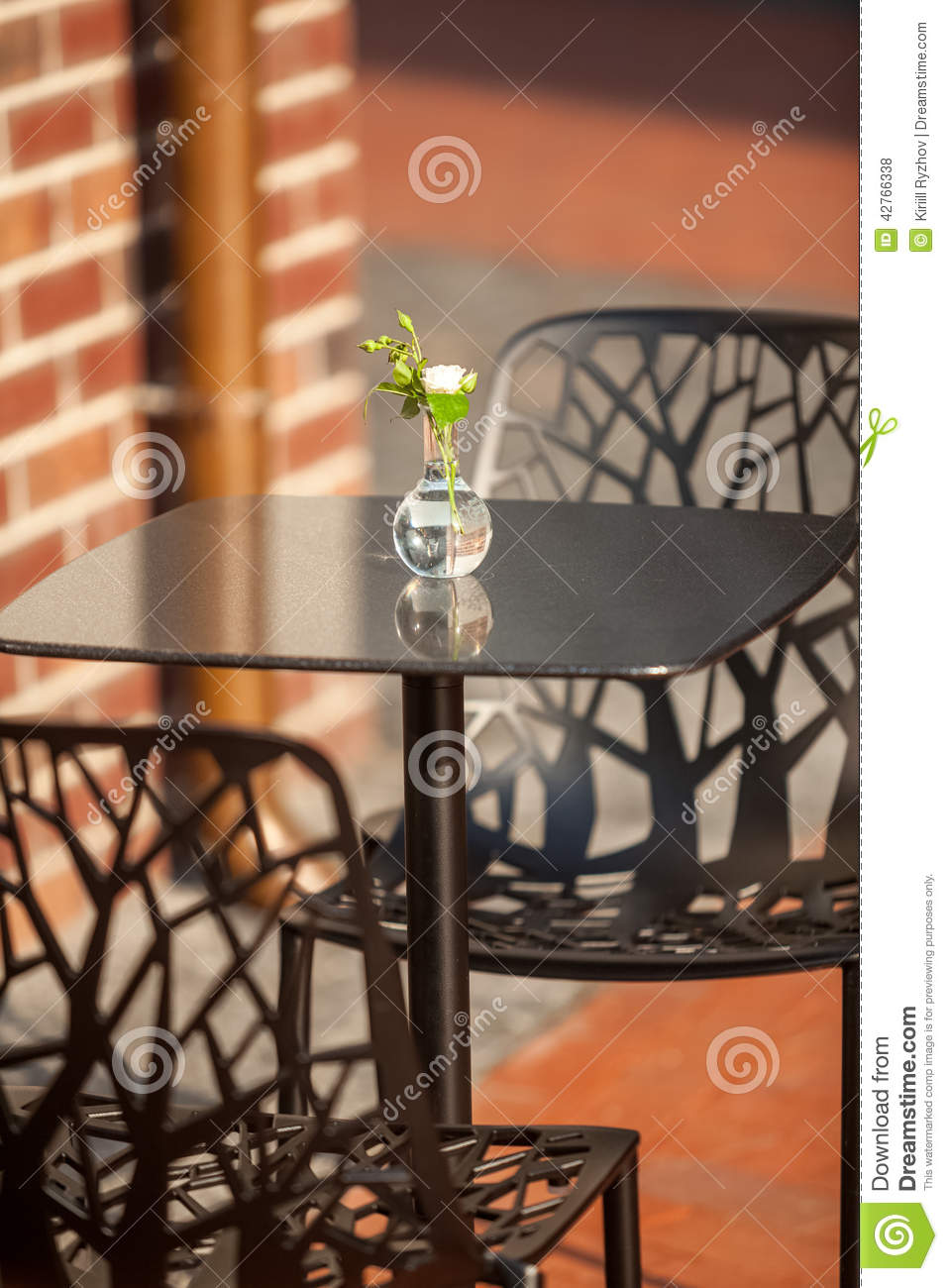 White flower in vase standing on table at outdoor cafe