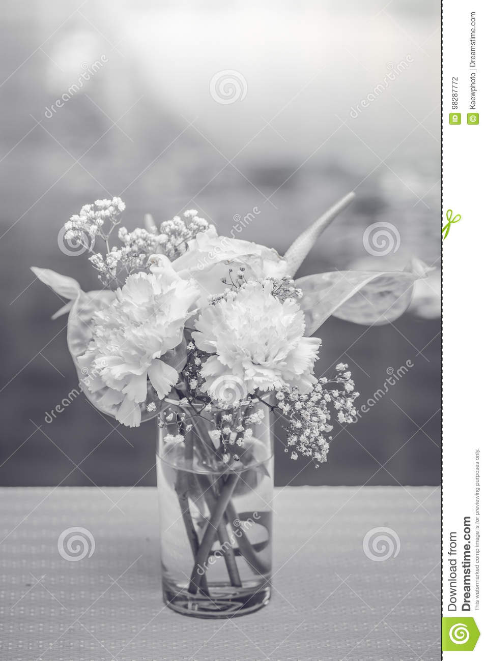 White Flowers In A Vase On The Coffee Table With A Black And Whi