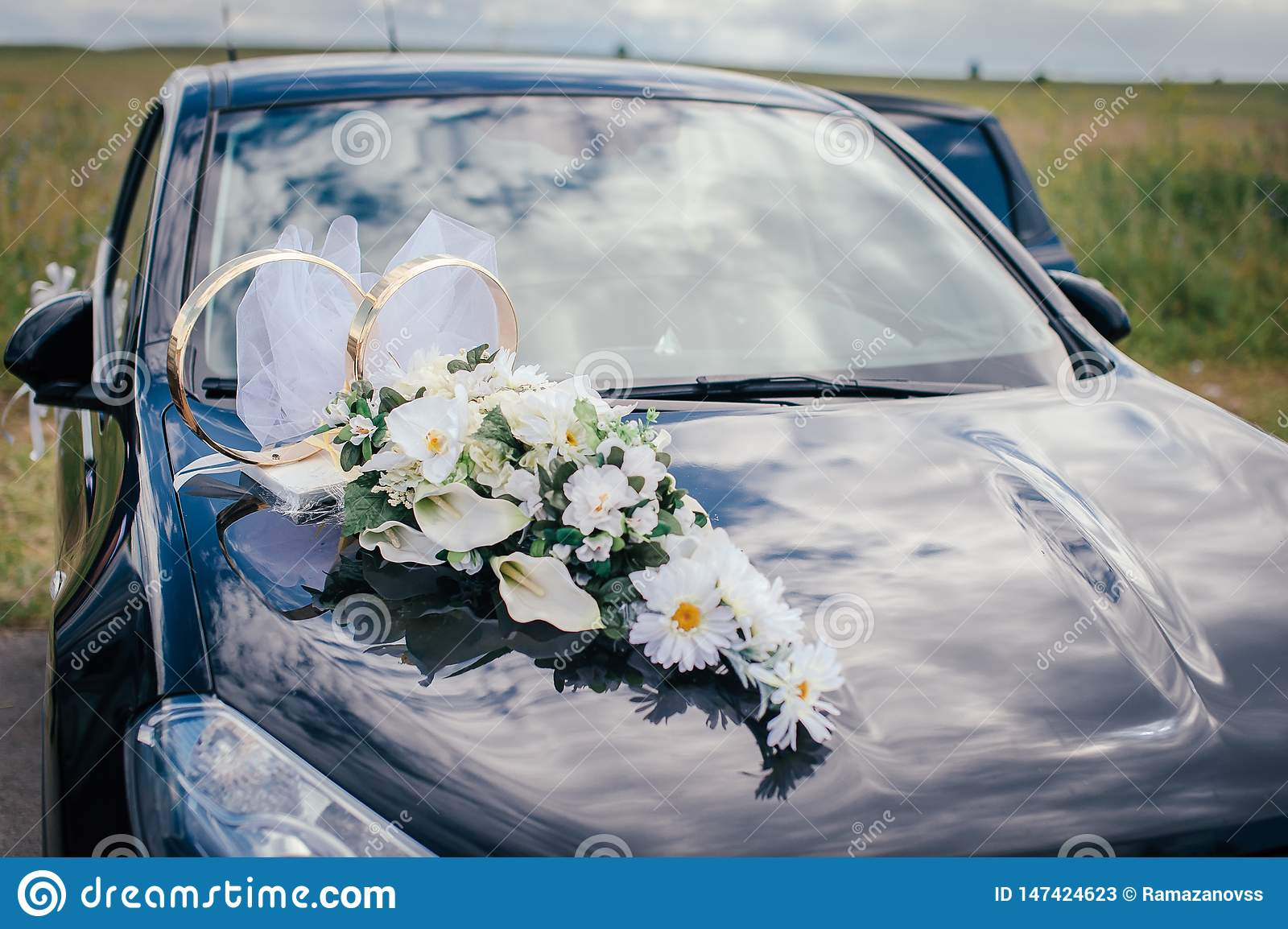 White flowers and wedding rings on the hood of the black car