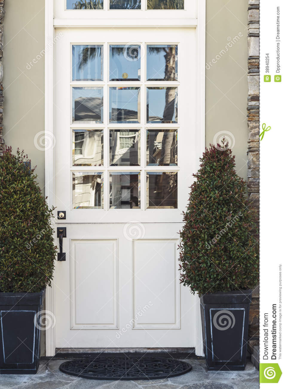 White front door to modern home flanked by plants stock Modern white front door
