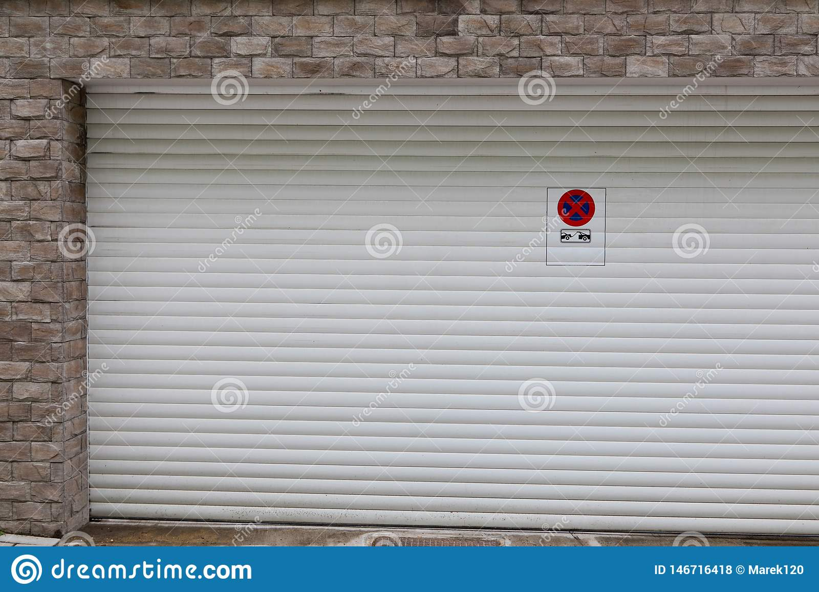 White garage door with no parking sign