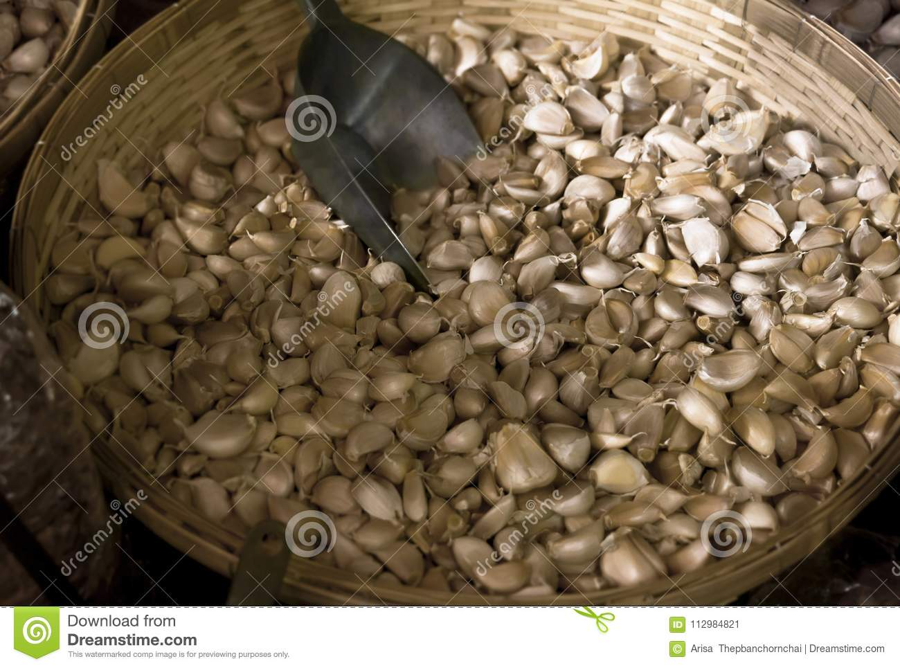 White garlic pile in basket for sale at the asian market. . Fresh garlic is one of the main ingredient in asian cuisine.