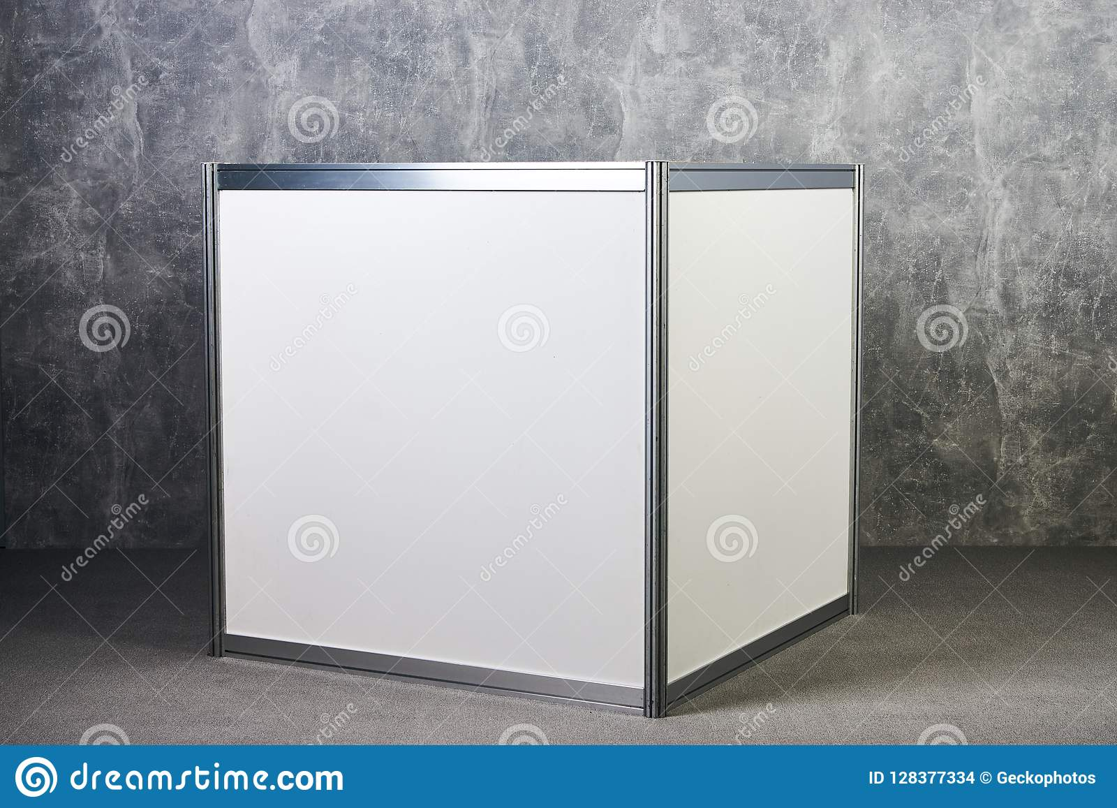White glass showcase stand against gray textured wall background international exhibition furniture elements in large warehouse interior