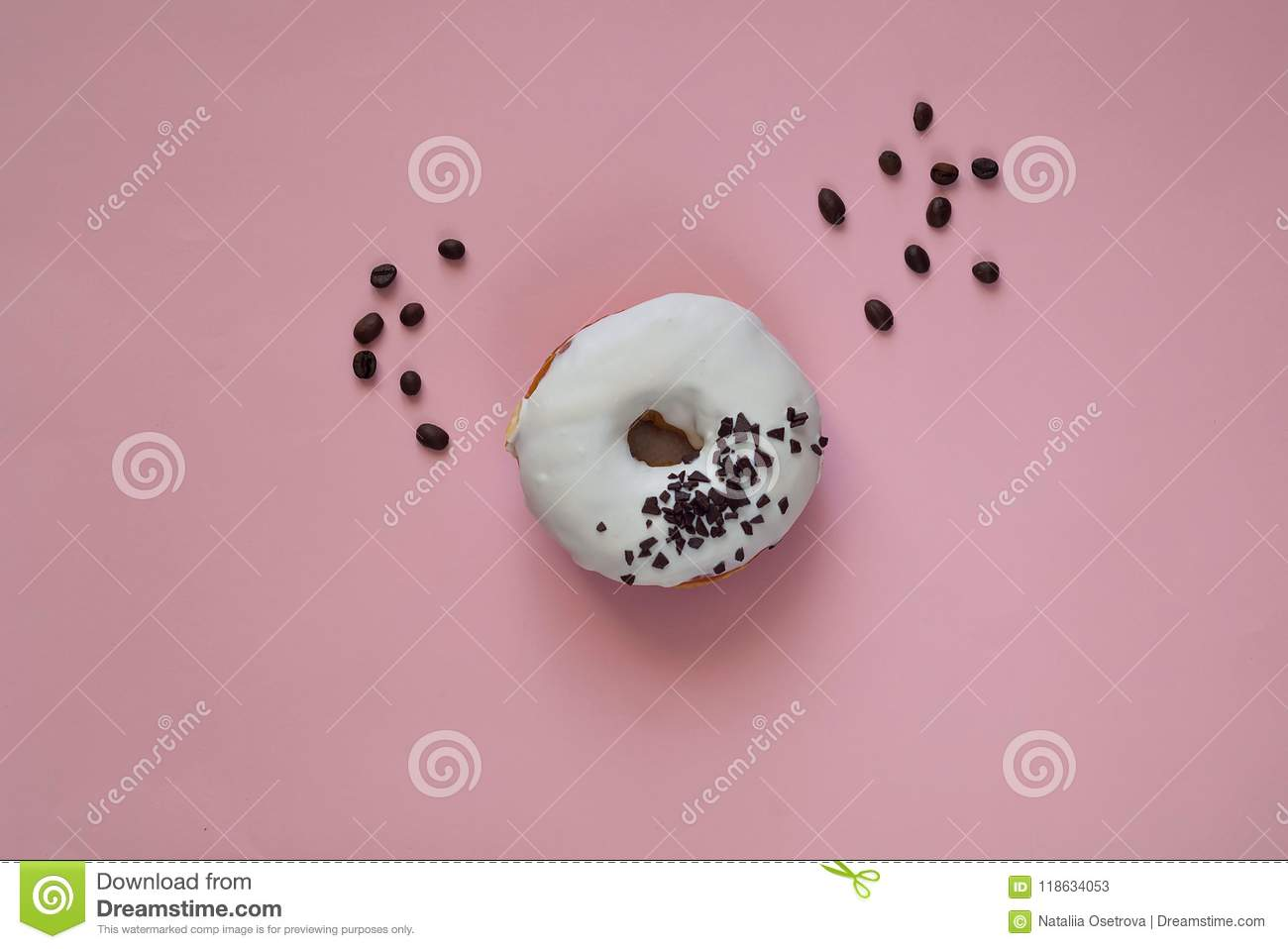 White glazed donut with black chocolate sweets on pink background.Flat lay. Food concept,colorful breakfast. Macro
