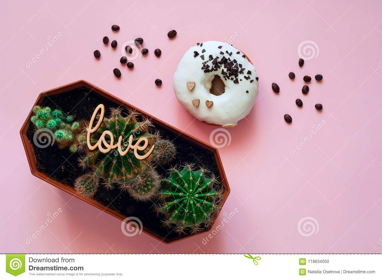 White glazed donut with black chocolate sweets with small cactuses. Food creative concept. Green Neon Mood on Pink background