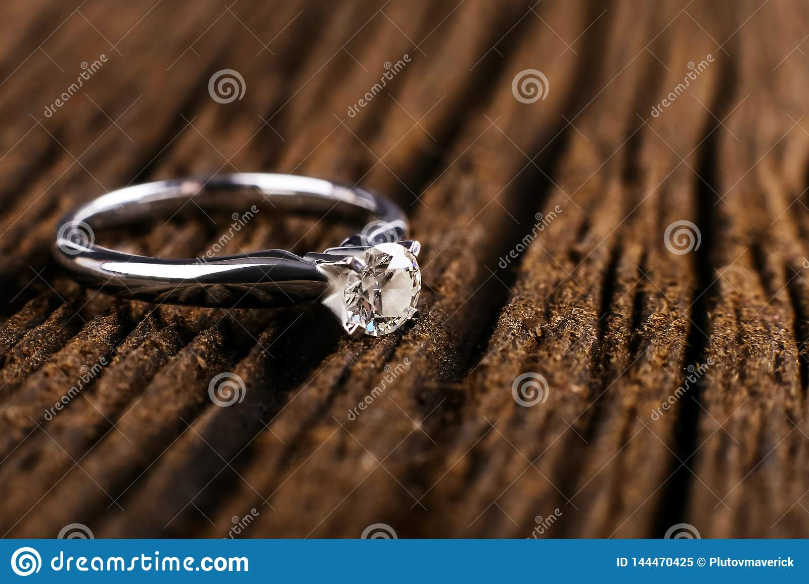 White Gold And Platinum Diamond Engagement Ring On A Wooden Table