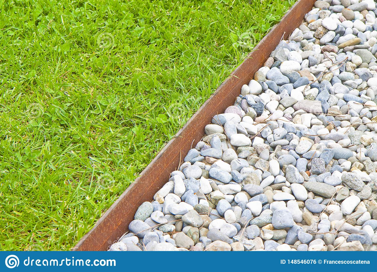 White gravel floor and fresh green lawn with clovers and rusty metal containment profiles