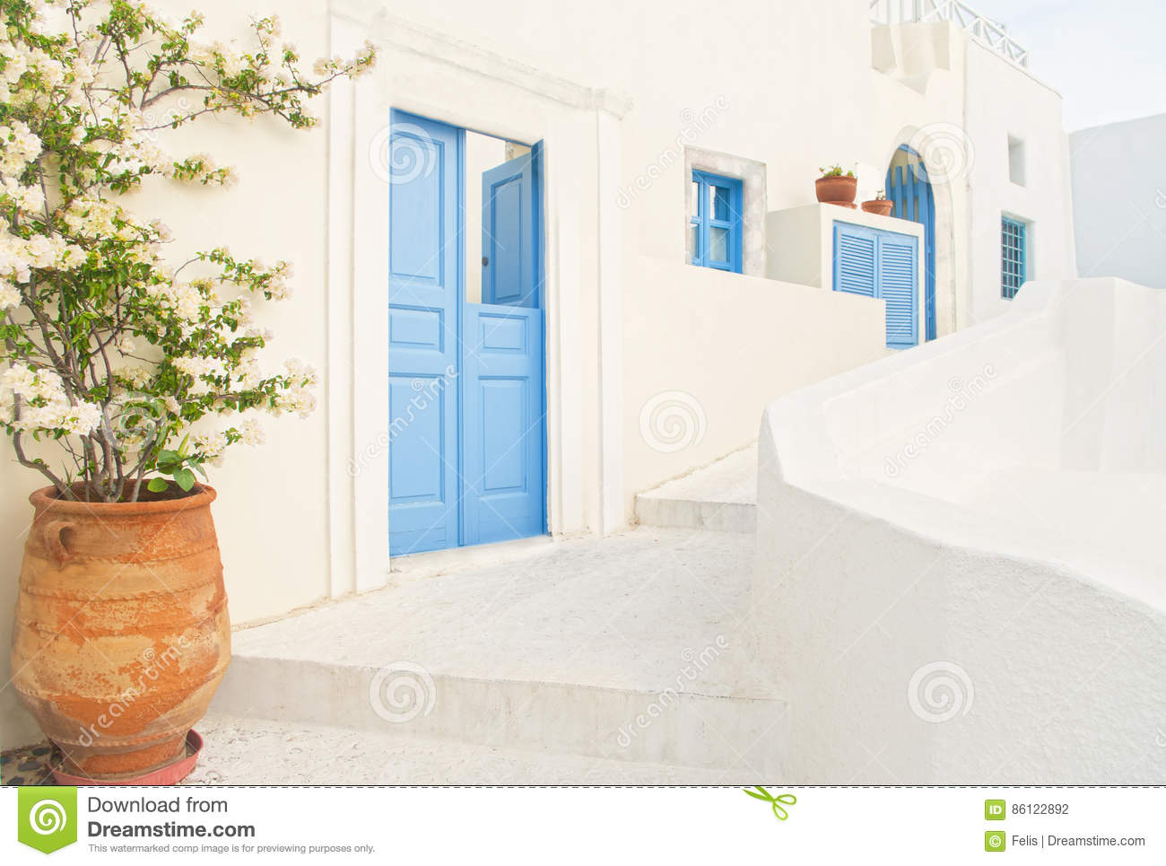 White Greek house with blue door and flower pot