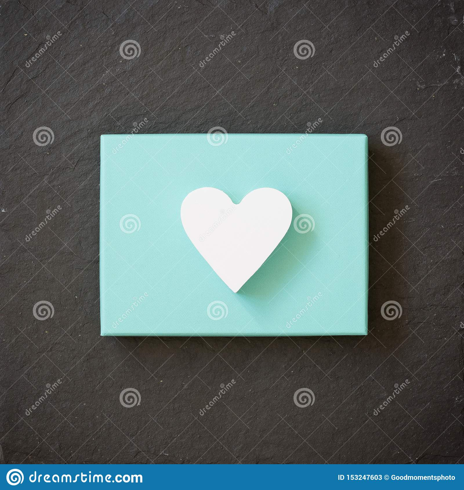 White heart on a turquoise color box on black background. Valentine`s day. Present. Gift