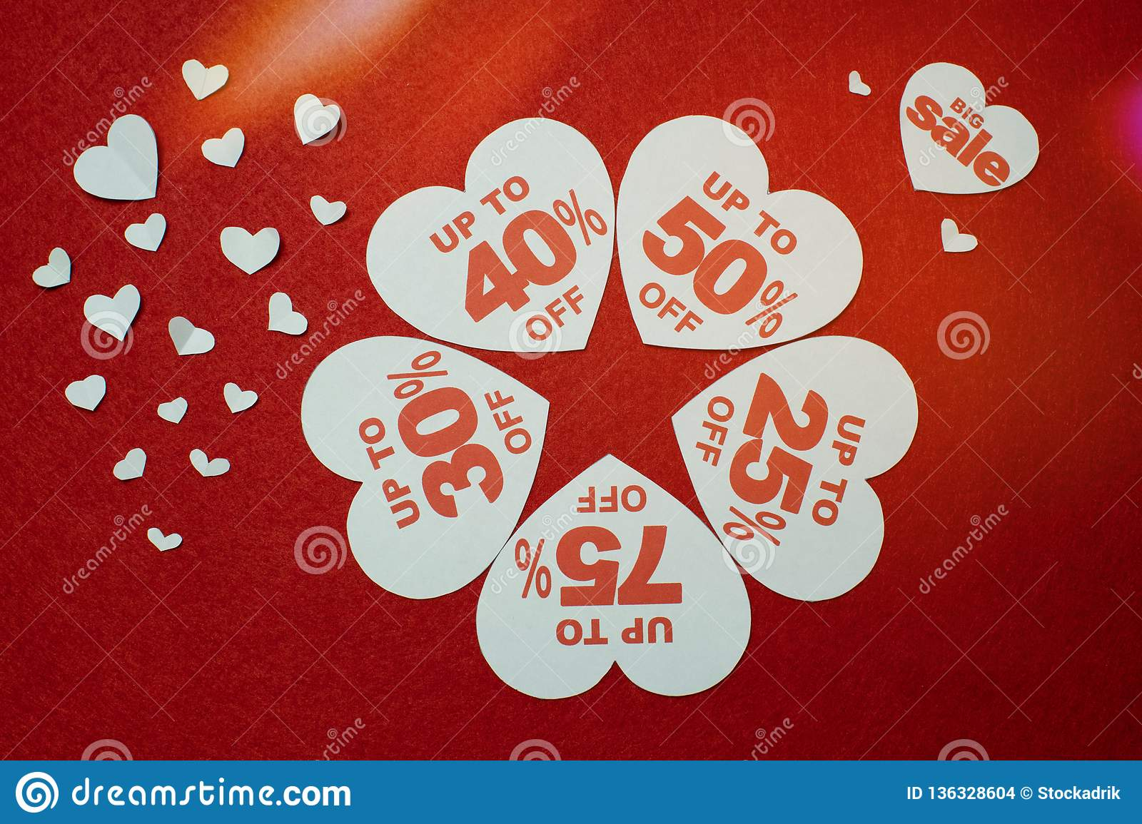 White hearts shaped sales promotion tag against a red background