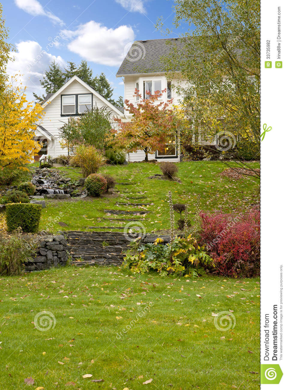 White horse farm American house during fall with green grass.