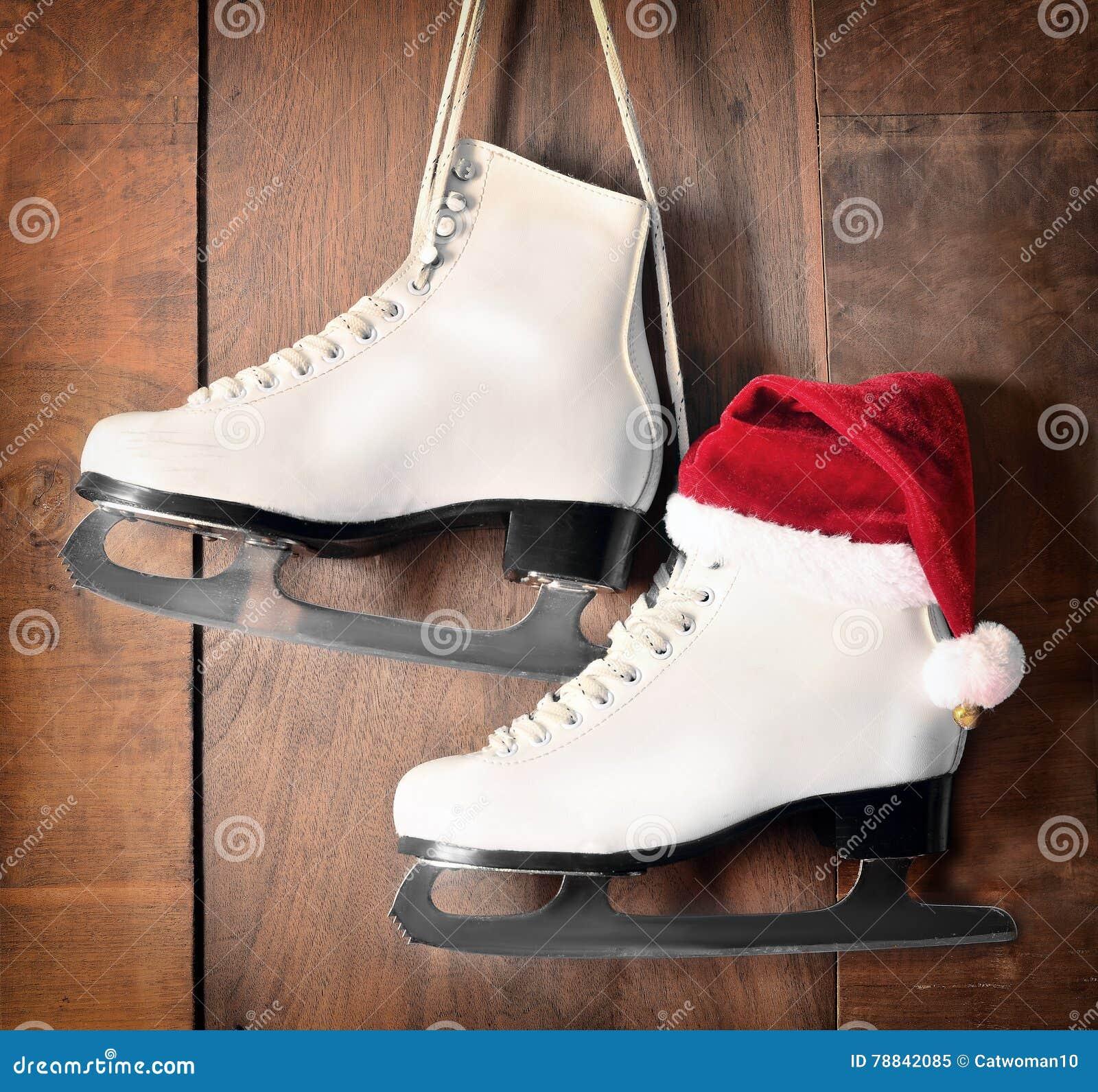 Roller skates for figure skating - White Ice Skates For Figure Skating Hanging On Wooden Background