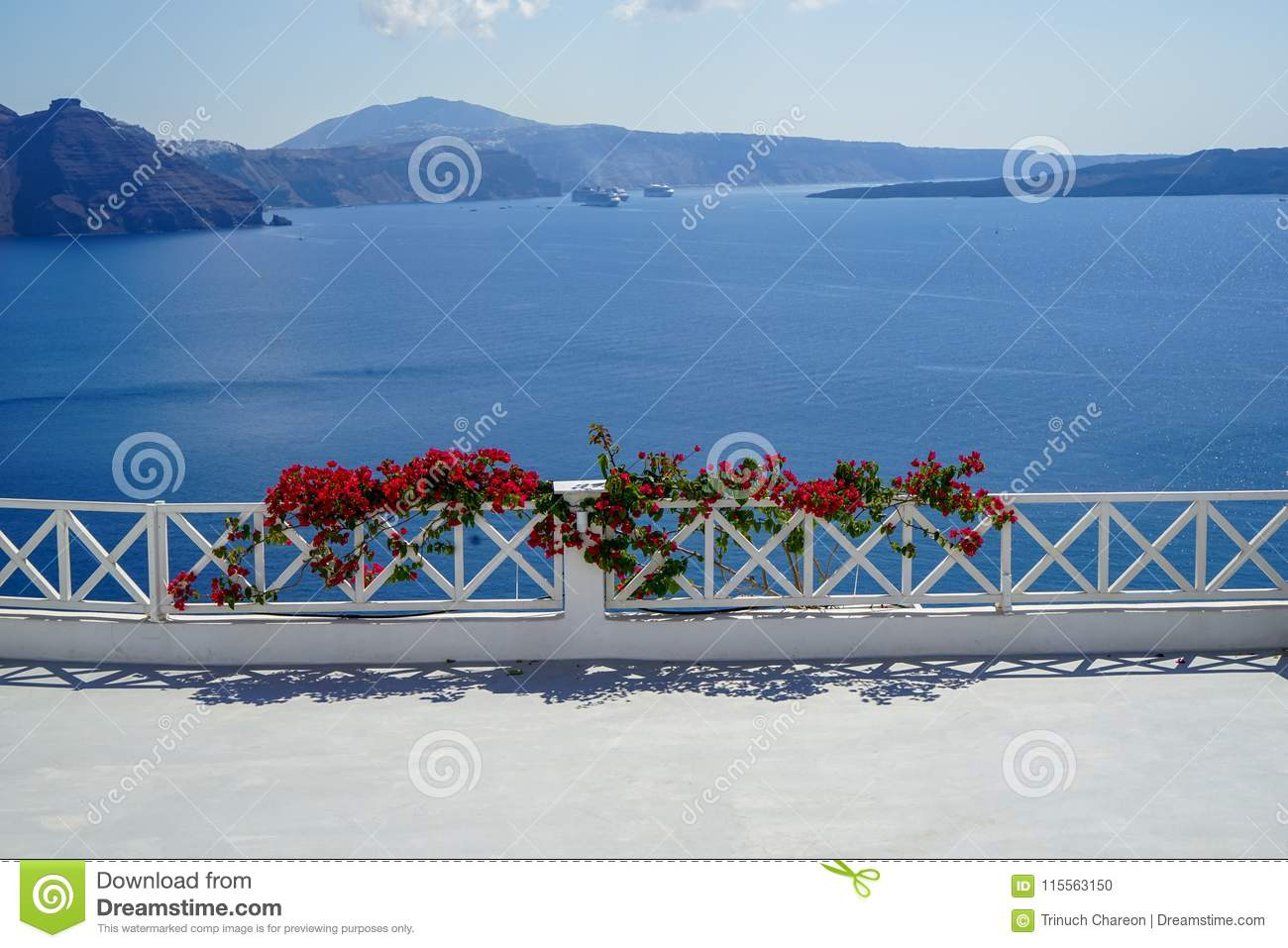 White island balcony with dark pink red Bougainvillea flower foreground in front of scenic mediterranean sea view and caldera