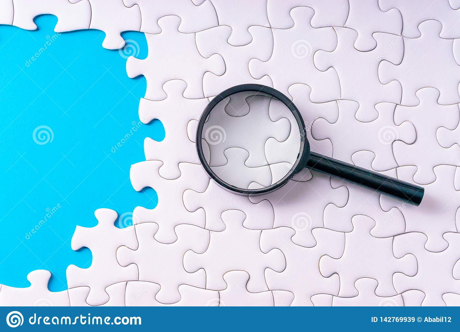 White jigsaw puzzle, Magnifier and missing pieces with selective focus and crop fragment