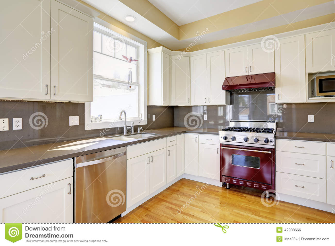 White kitchen with burgundy stove and grey counter tops for Burgundy kitchen cabinets