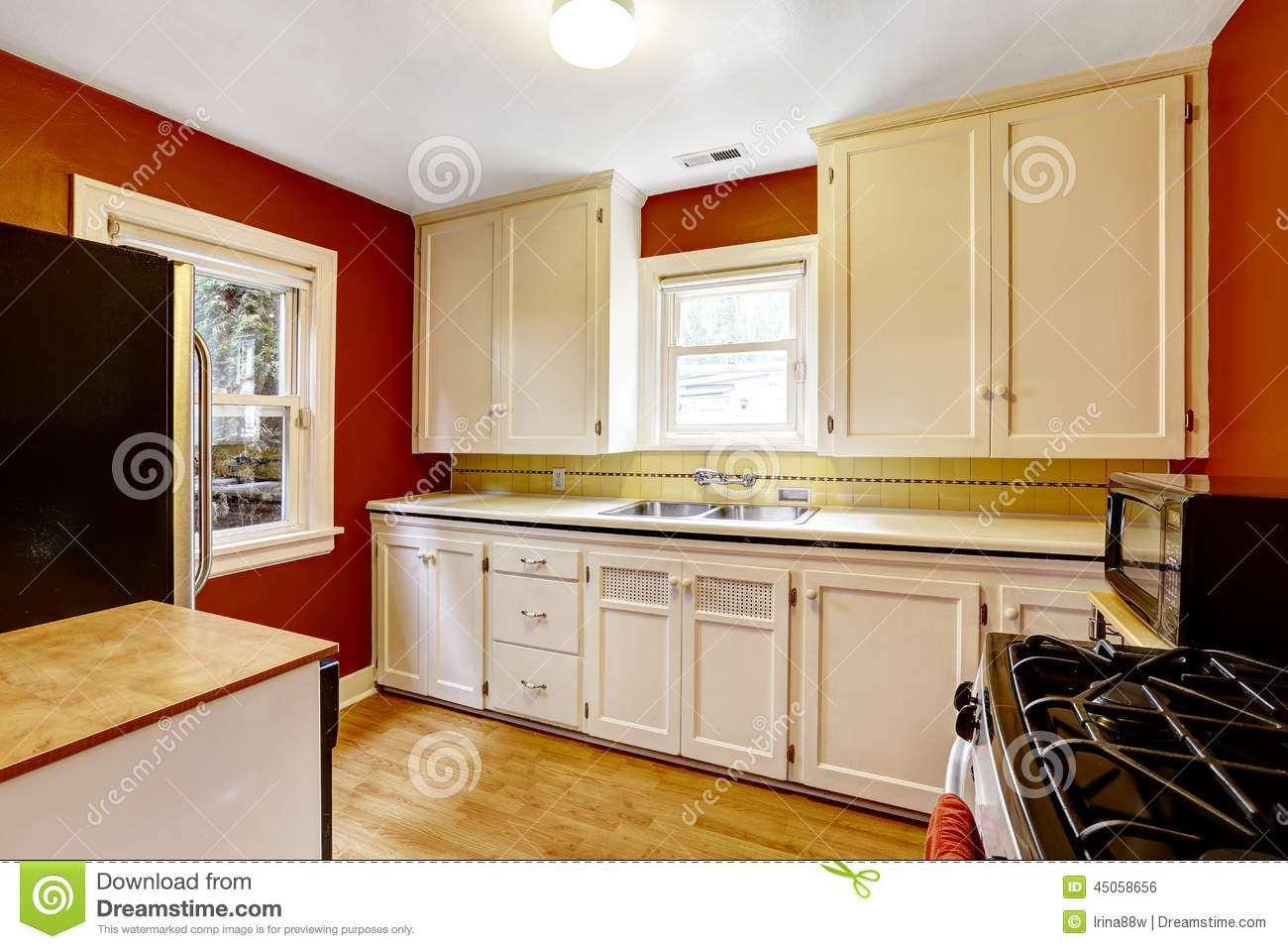 White kitchen cabinets with bright red wall stock photo for White cabinets red walls kitchen