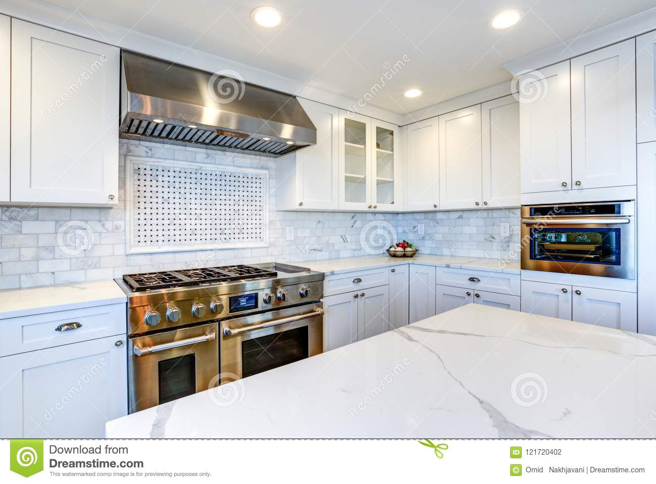 - White Kitchen With Stainless Steel Hood Over Gas Cooktop. Stock