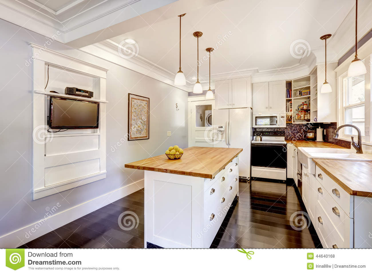 White Kitchen With Wooden Counter Top Island And TV Stock Photo ...