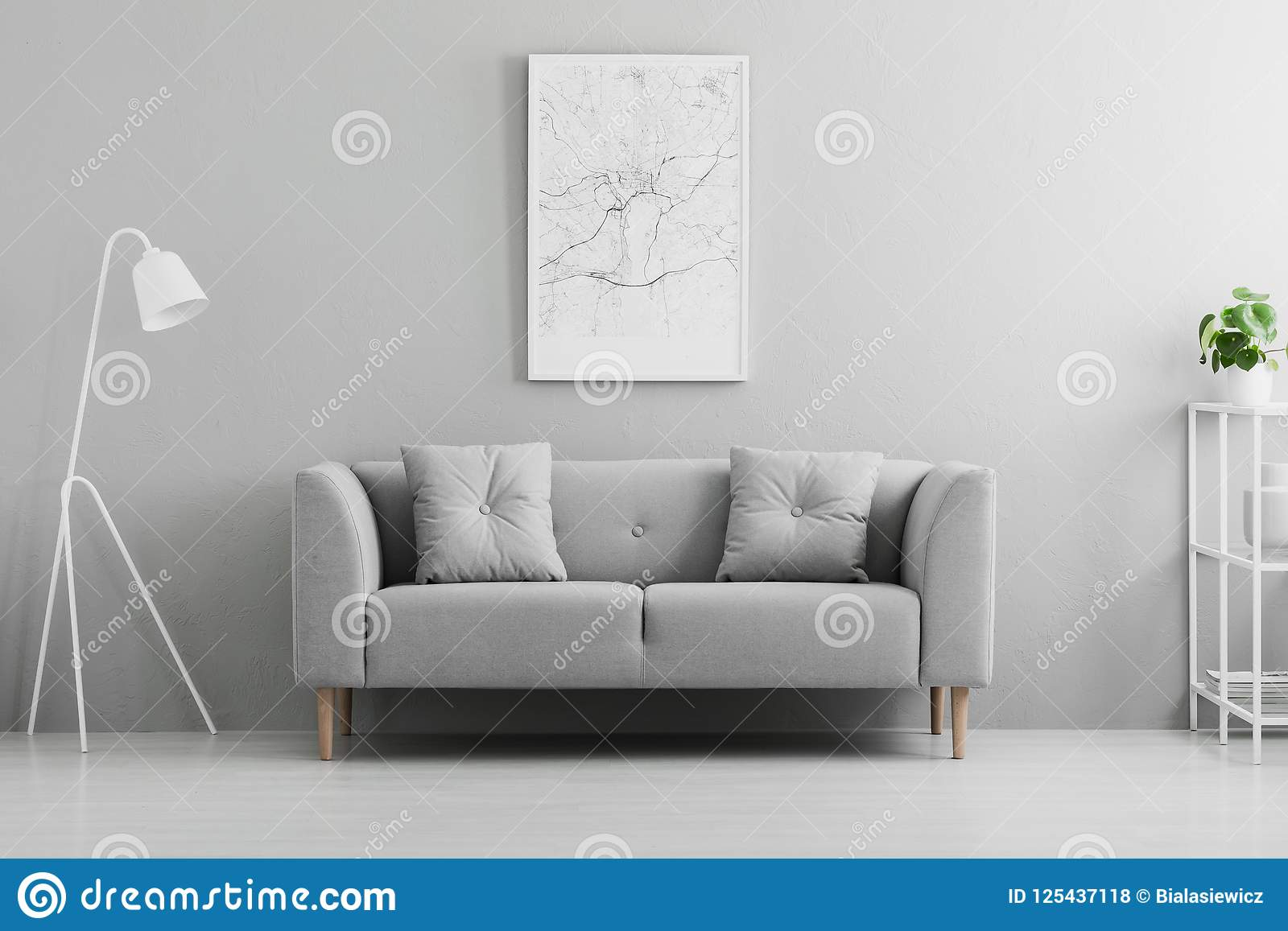 White lamp next to grey couch in minimal living room interior wi